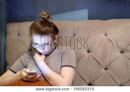 Pensive teen with smartphone on a sofa