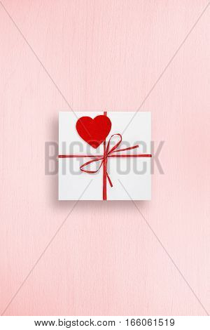 Gift box with red heart on pink background