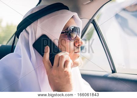 young arabian man sitting in the back of his car