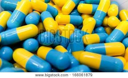 Two Tone Medicine Capsules On Stainless Steel Drug Tray, Yellow Blue Pills And Spatula