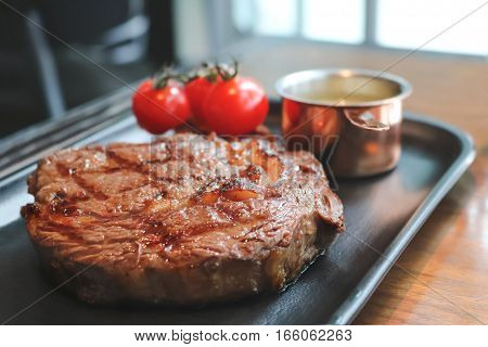 Close up of beefsteak on the tray in the restaurant, vintage tone.