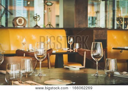 Interior of modern vintage restaurant in vintage tone, Empty glasses set on the table.