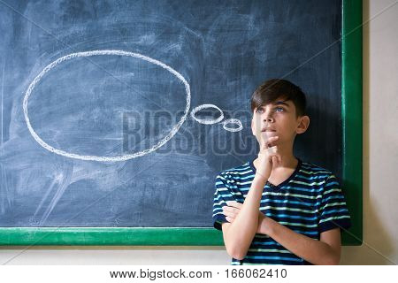 Concepts on blackboard at school. Intelligent and smart hispanic boy in class. Portrait of male kid thinking with hand on chin looking up against cloud drawing on blackboard