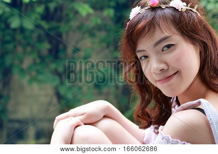 Young pretty Asian woman with flower headband in the park.