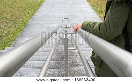 hand on railing : young girl using a railing to go downstairs at park