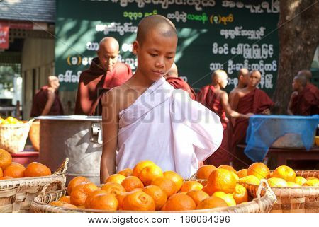 Mandalay Myanmar 17 January 2010: Young monk in the kitchen in front of a pile of oranges at Mahagandayon Monastery on Mandalay Myanmar