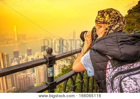 Traveler asian concept. Close up of young photographer with professional camera from back, photographing the Victoria Harbour from Victoria Peak, the highest mountain in Hong Kong. Shot at sunset.
