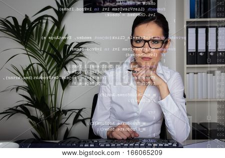 young woman sitting in front of her computer, programming. the code she is working on can be seen through the screen.