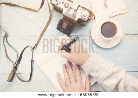 woman hand pen and coffee and camera on table