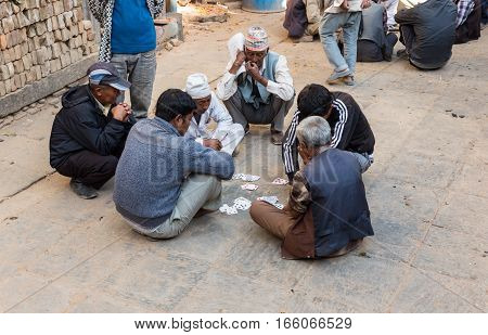 BHAKTAPUR, NEPAL - November 15, 2016: The local people are playing cards in the street, Bhaktapur, Nepal.