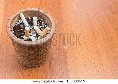 cigarette in ashtray on wooden background with copy space