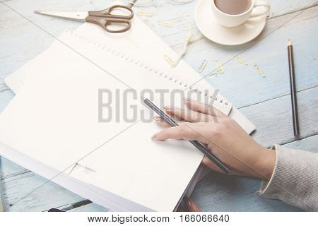 woman hand pencile and coffee cup blank notebook on wooden table