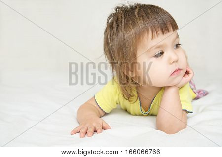 Thoughtful Child , Thinking Little Girl Lying On Bed Looking Awa