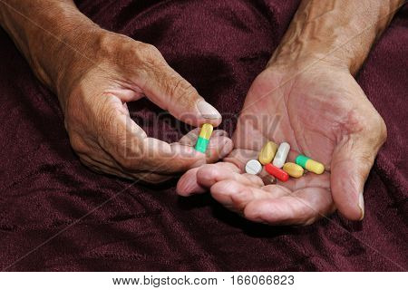 Many colorful pills in the older hands. Painful old age. Health care of older people