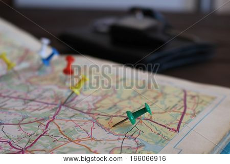 Travel destination points on a map indicated with colorful thumbtacks and shallow depth of field with space for copy. The keys to the car in the blur in the background.