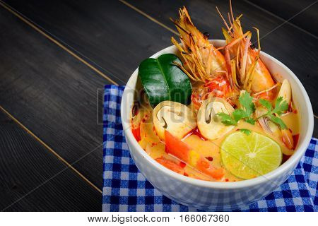 Closeup Tom Yum Soup or River Prawn Spicy Sour Soup (Tom Yum Goong) on wooden table with blue tablecloth Thai local food