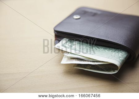 leather wallet with dollar bills on wooden table