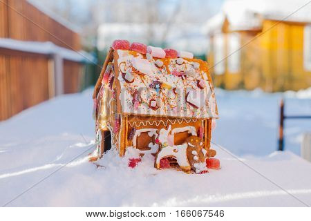 Gingerbread house stands in the snow. Candy sweet