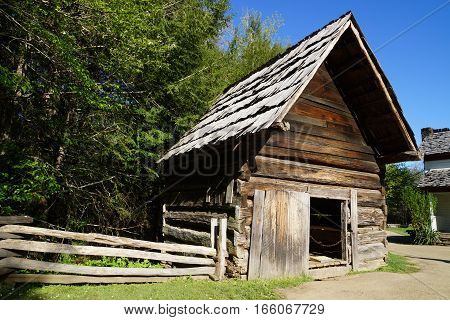 Old wood shed with steep A-line roof with split rail fence on dirt road, off center