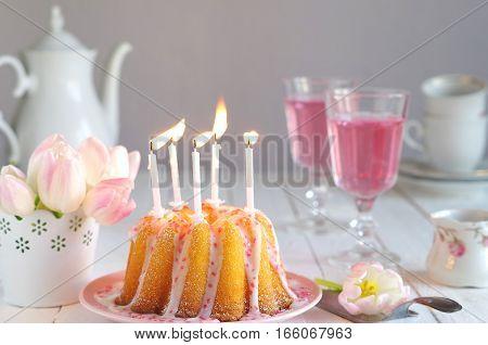 birthday cake gugelhupf with sugar glaze and sugar sprinkles