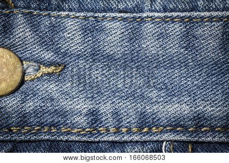 Denim jeans texture or denim jeans background with seam and studs. Old grunge vintage denim jeans. Stitched texture denim jeans background of fashion jeans design. Dark edged.