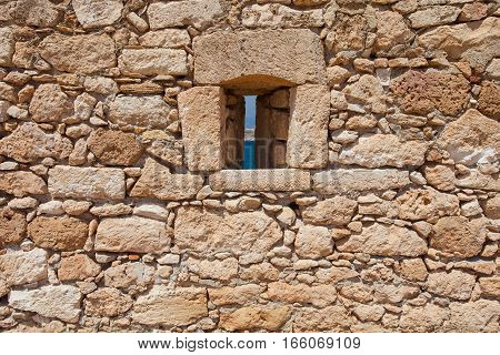 Rethymnon Island Crete Greece - June 23 2016: View on the stone wall with a narrow window of Fortezza Castle in Rethymnon