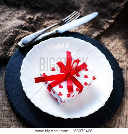 Valentines day table setting with white plate fork knife and red heart on old wooden table