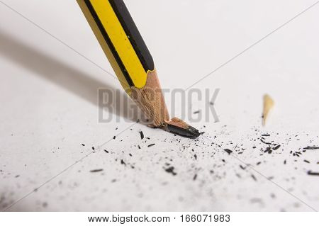 Snapped and broken pencil tip on a paper