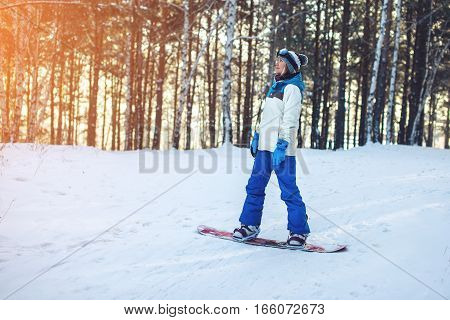 female snowboarder snowboarding down the mountain among the trees at sunset concept of sport and active lifestyle
