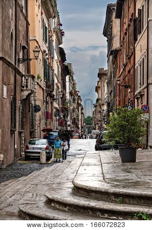 Rome Italy - June 10 2016: Two women walking together on a narrow residential side street in the city of Rome. Rome is the capital of Italy with 2.9 million residents.