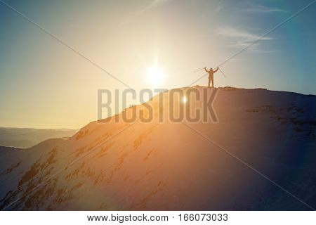 man hikers tourist celebrating success standing on top at the peak of a snowy mountain at sunset the concept of the path to purpose and success