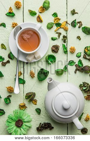 White teapot and cup with tea on green table decorated dried flowers