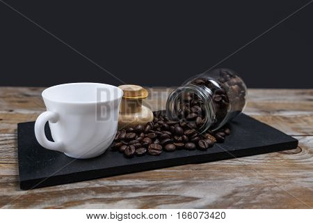 Coffee beans coming out of the jar next to a rate and on a slate tray