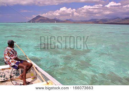 TAMARIN BAY, MAURITIUS - NOVEMBER 23, 2012: A fisherman on his boat in Tamarin Bay