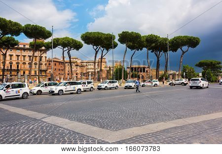 Rome Italy - June 10 2016: Taxi's lined up waiting for customers along a busy main road Via dei Fori Imperiali which leads to the historic Colosseum.