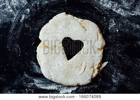 Small heart cut out of dough rolled on a table. Horizontal studio shot.