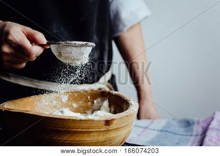 Person adds flour to a pastry through the strainer. Vertical studio shot.