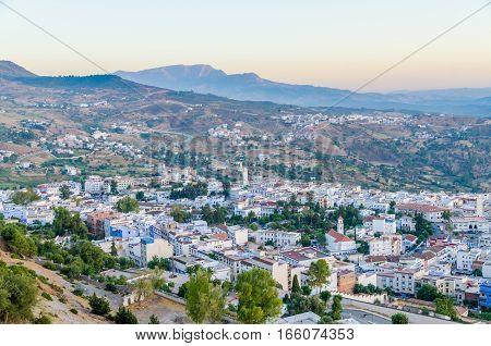 Beautiful historical town Chefchaouen with its blue washed buildings viewed from a hill during sunset, Morocco, North Africa.
