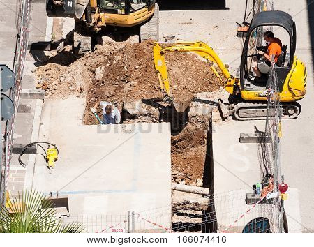 UdineItaly - June 28 2016 : Men at work with excavator to do the excavation for the laying of drains of a sewer.
