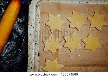 Cookies on baking pan and rolling pin on the kitchen table