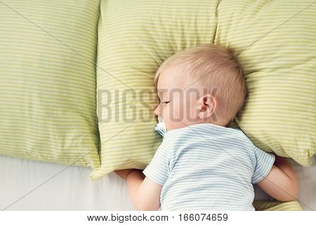 One year old baby lying in the bed with green bedding