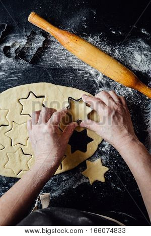 Person shaping the cookies with the form. Horizontal studio shot.