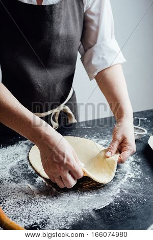Person rolling a piece of dough with hands. Vertical studio shot.