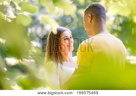 Young couple hugging among trees - photographed through leaves