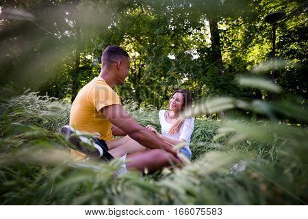Wide angle photo of young couple talking together on date in nature