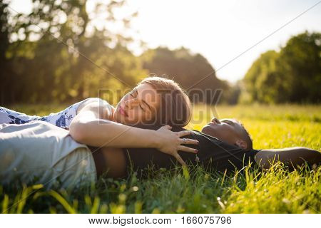 Young multi ethnic couple resting in grass on sunny day