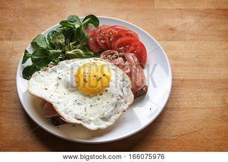 Fried egg on bread with ham garnished with green salad and tomatoes on a white plate on a wooden table generous copy space selective focus narrow depth of field
