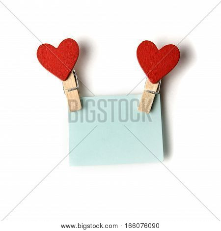 clothespins with red hearts holding a blue sticker.