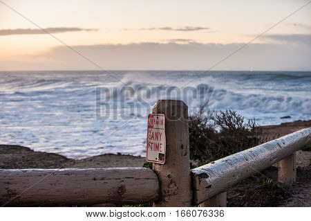 No parking sign with large winter swell waves in background.