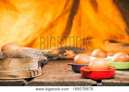 Fresh eggs on various colors ceramic plates next to sieve on rustic table